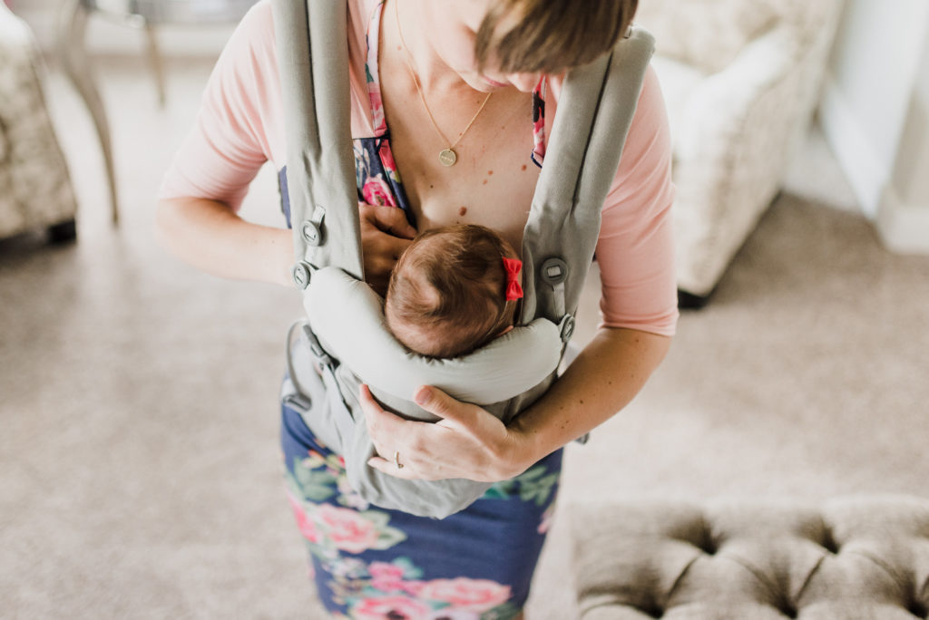 woman breasfeeding her child using a carrier